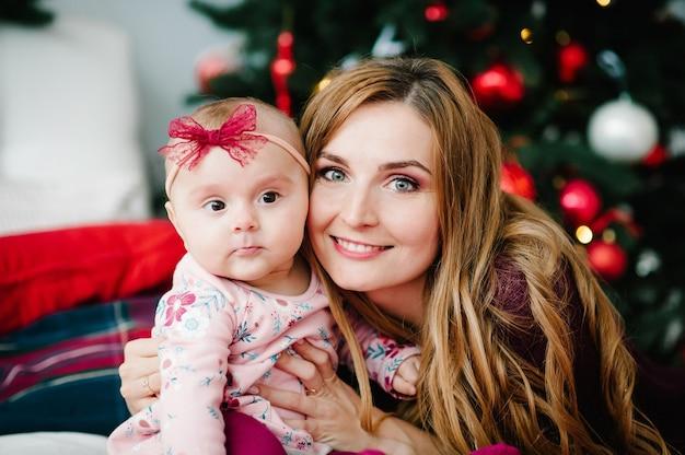 Babymeisje met moeder op bed in de buurt van de kerstboom