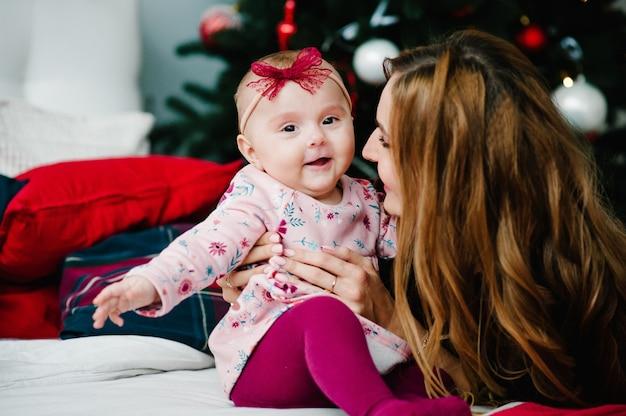 Babymeisje met moeder op bed in de slaapkamer in de buurt van de kerstboom. vrolijk kerstfeest. kerst versierd interieur. het concept van gezinsvakantie.