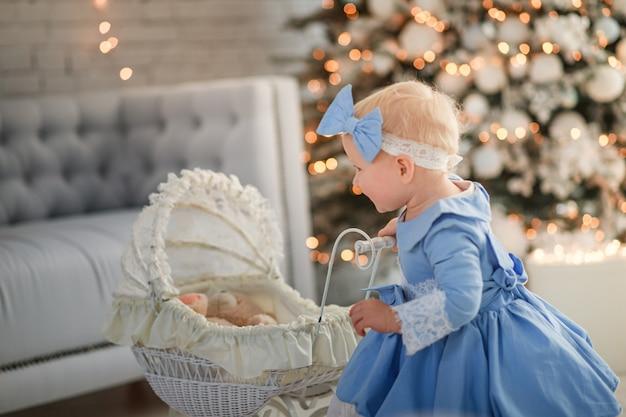 Babymeisje met schattige jurk en hoofdband draagt kinderwagen in feestelijk versierde kamer
