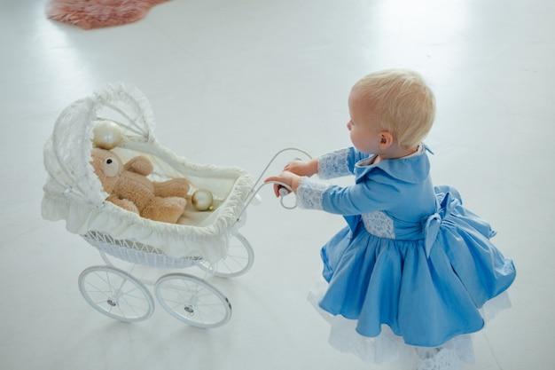 Babymeisje met schattige jurk en hoofdband draagt kinderwagen in feestelijke kamer met slinger