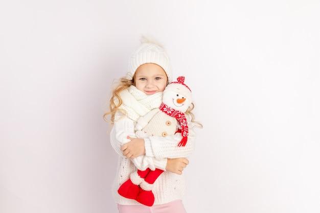 Babymeisje met sneeuwpop speelgoed in warme muts en trui op witte geïsoleerde achtergrond, plaats voor tekst