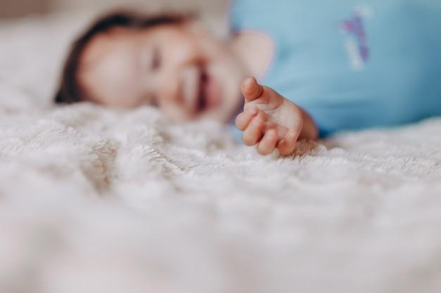 Babymeisje of jongen die op bed in witte bladen kruipen
