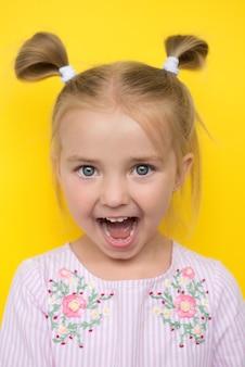 Babymeisje op geel, toont emoties van verbazing