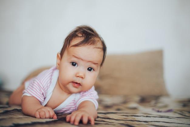 Babymeisje op haar maag. met verbaasde uitdrukking opkijken