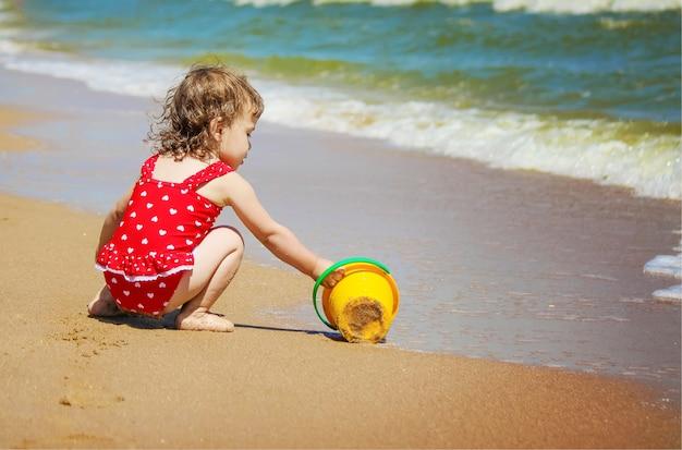 Babymeisje op het strand, door de zee. selectieve aandacht.