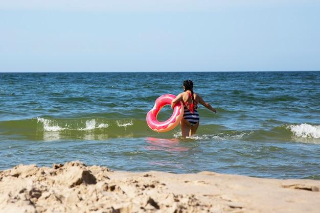Babymeisje op zee met een roze reddingsboei op een zomerdag, vakantie