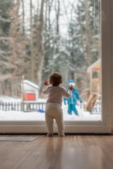 Babymeisje permanent bij een raam kijken naar haar broer buiten spelen in de wintersneeuw in de tuin.