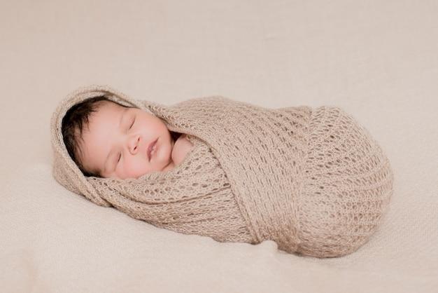 Babymeisje slaapt bedekt met een delicate beige deken