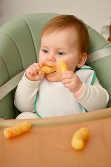 Babymeisje snacks eten in haar voedende stoel