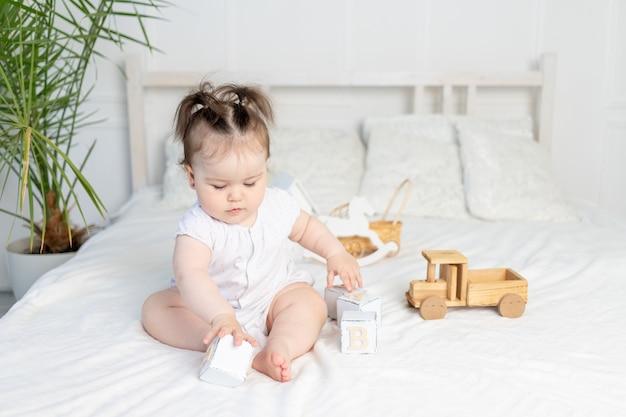 Babymeisje speelt met houten speelgoedblokjes op het bed thuis in een lichte kamer, het concept van de ontwikkeling van de vroege kinderjaren