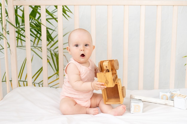 Babymeisje speelt zes maanden met een houten typemachine in een wieg in een roze bodysuit, vroeg ontwikkelingsconcept