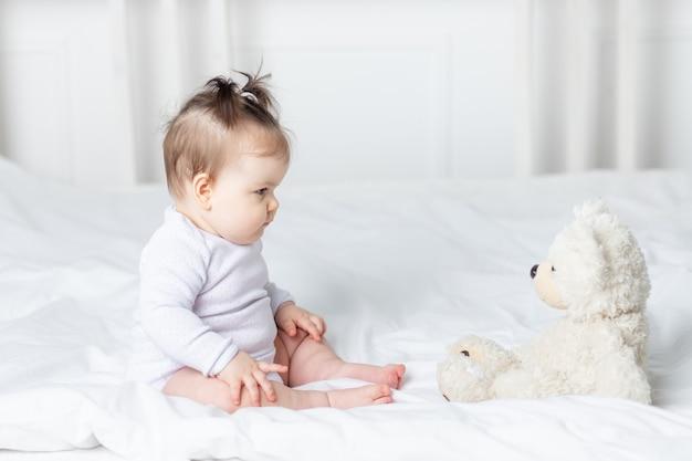 Babymeisje spelen met een teddybeer speelgoed op het bed thuis, het concept van spelen en ontwikkeling van kinderen