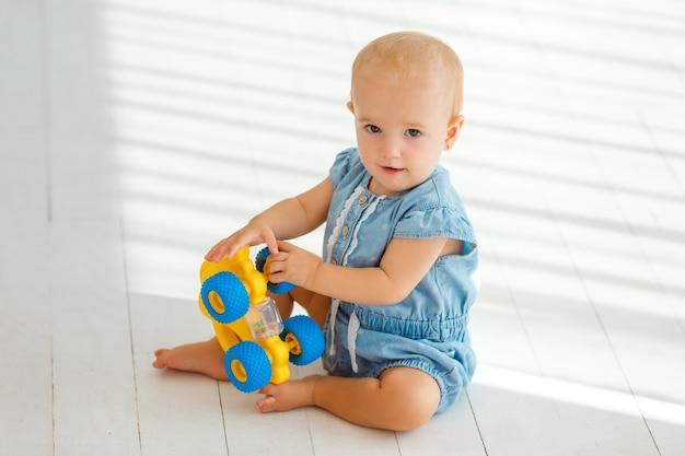 Babymeisje spelen met gele speelgoed olifant. kleine peuter glimlachen