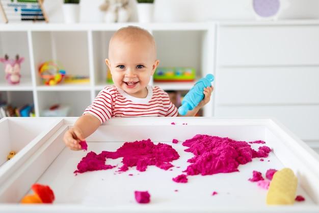 Babymeisje spelen met kinetisch zand