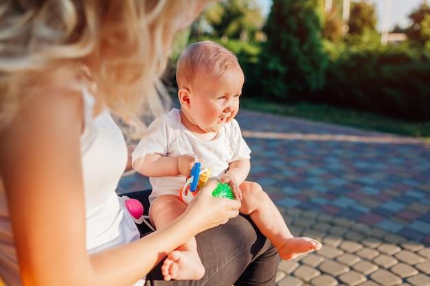 Babymeisje spelen met speelgoed zittend op de knieën van haar moeder in zomer park.