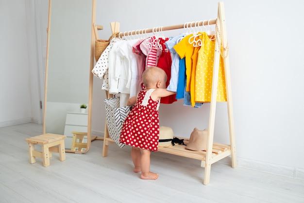 Babymeisje staat in de buurt van een kledingkast en kiest een jurk.