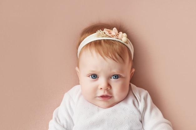 Babymeisje van vier maanden ligt op een lichtroze muur