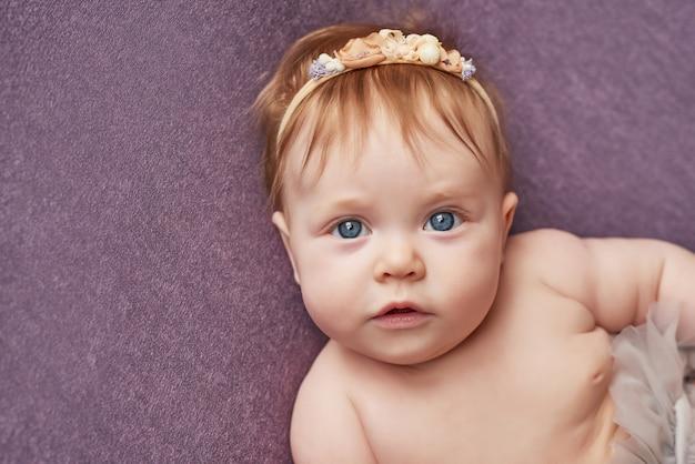 Babymeisje van vier maanden ligt op een paarse muur