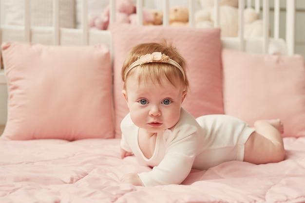 Babymeisje van vier maanden ligt op een roze muur