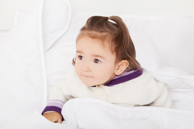Babymeisje verstopt zich onder de witte deken