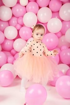 Babymeisje viert haar eerste verjaardag. meisje op achtergrond van roze ballonnen. bovenaanzicht
