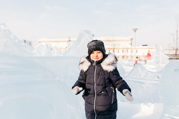 Babymeisje wandelen in de winter, ijssculpturen van de winter, hoed en warme jas