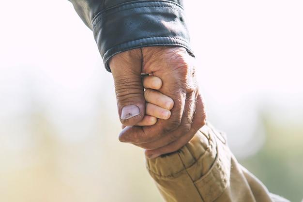 Babymeisje warme jas en pet c grootvader handen in herfst park