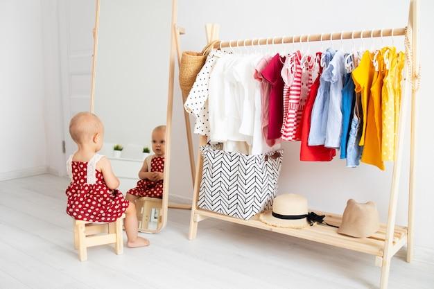 Babymeisje zit en loking in de spiegel