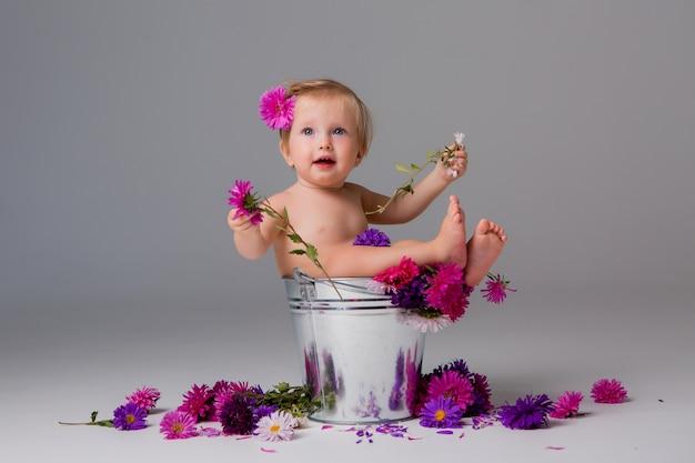Babymeisje zit in een emmer bloemen