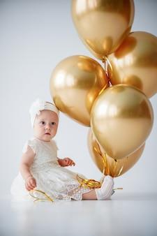 Babymeisje zit met een bos van gouden ballonnen