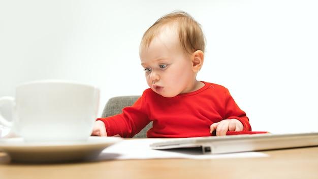 Babymeisje zit met kopje koffie en toetsenbord