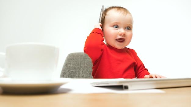 Babymeisje zit met pen en toetsenbord