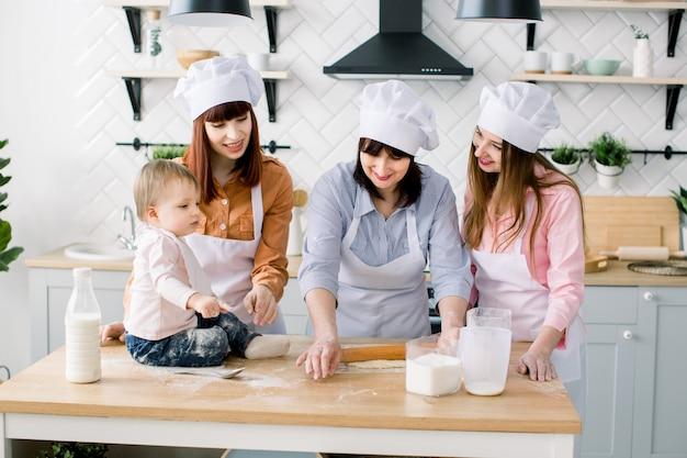 Babymeisje zit op de houten tafel in de keuken terwijl haar moeder, tante en grootmoeder het deeg voor koekjes maken. gelukkige vrouwen in witte schorten samen bakken