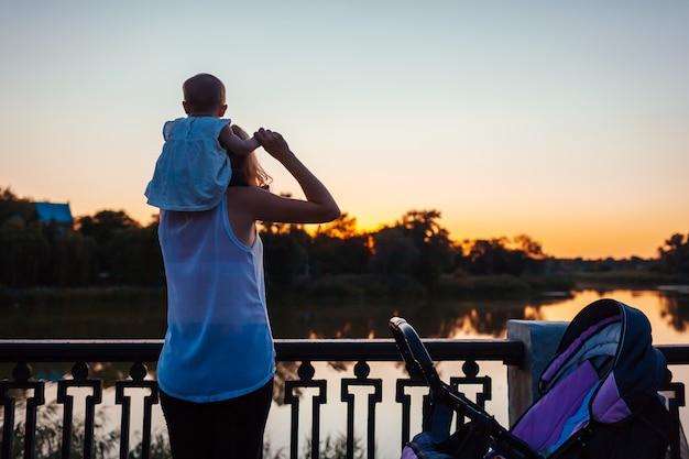Babymeisje zit op de schouders van haar moeder en bewondert landschap.