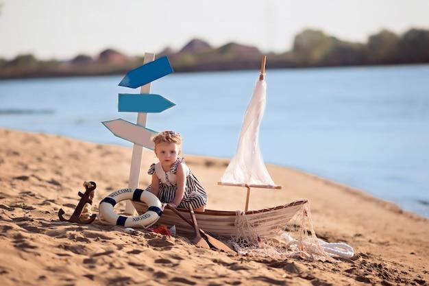 Babymeisje, zittend in een boot op een strand