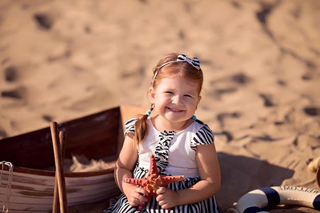 Babymeisje zittend in een boot, verkleed als zeeman, op een zandstrand met schelpen aan zee