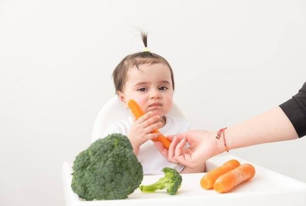 Babymeisje zittend in een kinderstoel wortel en broccoli eten.