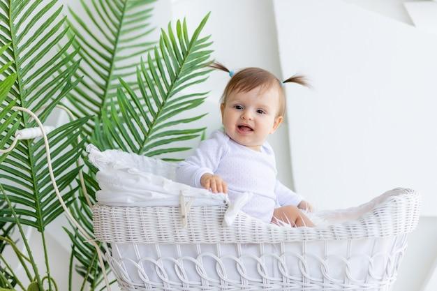 Babymeisje, zittend in een mooie wandelwagen in een witte romper thuis