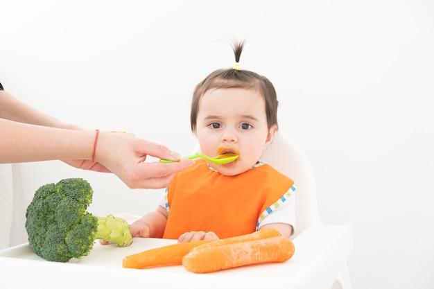 Babymeisje zittend in een stoel childs plantaardige puree eten. moeder voedt de baby.