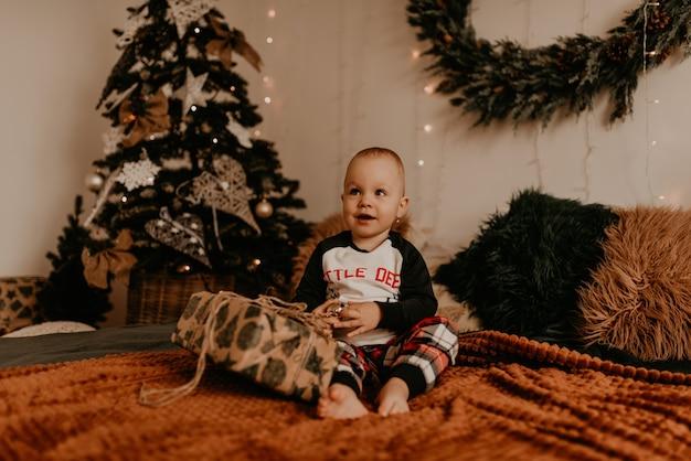 Babymeisje zittend in pyjama's op het bed in de slaapkamer en opent een geschenk. kerstochtend. nieuwjaars interieur. valentijnsdagviering