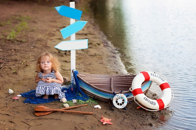 Babymeisje zittend op een strand in de buurt van een boot