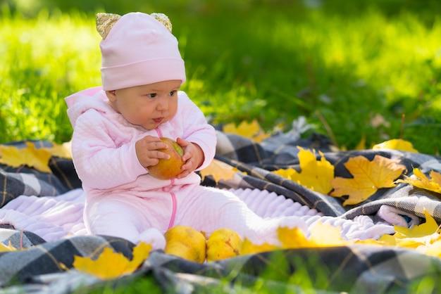 Babymeisje zittend op een tapijt omringd door kleurrijke gele herfstbladeren in de schaduw van een boom op weelderig groen gras met een gouden appel