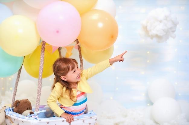 Babymeisje, zittend op een wolk naast een mand met ballon in de wolken