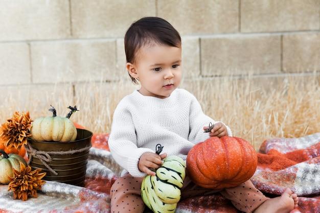 Babymeisje zittend op een zachte deken en kleurrijke pompoenen buiten te houden