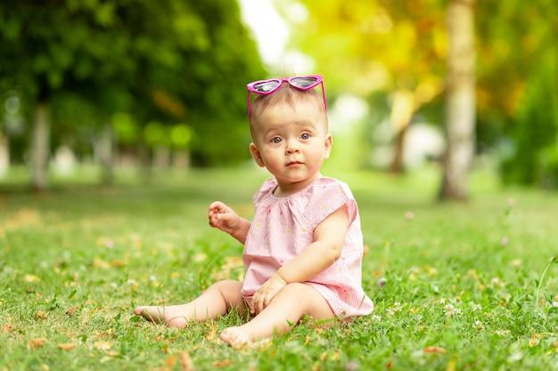 Babymeisje zittend op het groene gras in een roze romper en heldere glazen, wandelen in de frisse lucht