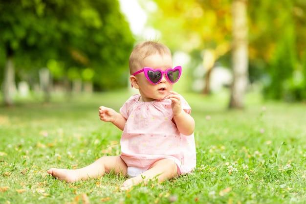 Babymeisje zittend op het groene gras in een roze romper en heldere glazen, wandelen in de frisse lucht Premium Foto