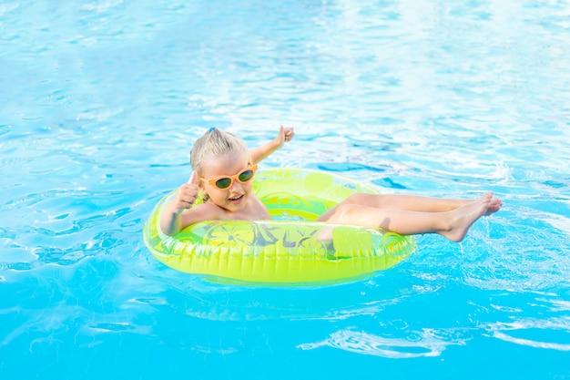 Babymeisje zwemt in de zomer in het zwembad met een opblaasbare gele cirkel en toont de klas, het concept van reizen en recreatie