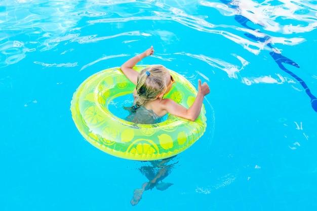 Babymeisje zwemt in het zwembad met een opblaasbare gele cirkel in de zomer en toont klasse, achteraanzicht, reis- en vrijetijdsconcept