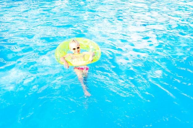 Babymeisje zwemt in het zwembad met een opblaasbare gele cirkel in de zomer, het concept van reizen en recreatie, een plek en ruimte voor tekst