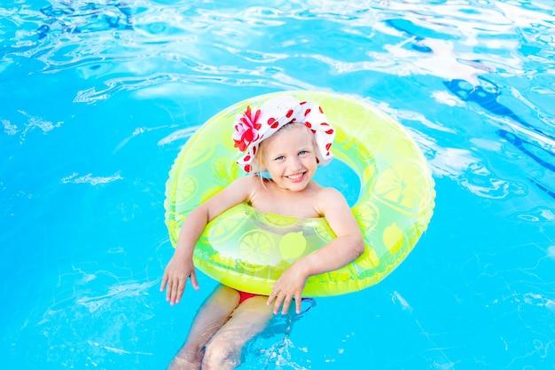 Babymeisje zwemt in het zwembad met een opblaasbare gele cirkel in de zomer, het concept van reizen en recreatie en glimlacht in panama